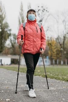 Вид спереди пожилой женщины с медицинской маской и треккинговыми палками на открытом воздухе