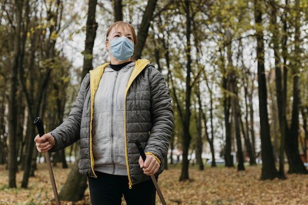 의료 마스크와 트레킹 스틱 야외 수석 여자의 전면보기