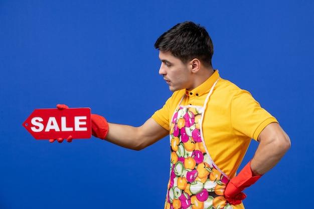 파란색 벽에 판매 표지판을 들고 있는 노란색 티셔츠를 입은 진지한 남성 가사도우미의 전면 모습