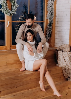 Вид спереди серьезного мужчины обнимает свою очаровательную девушку, сидящую на деревянной лестнице