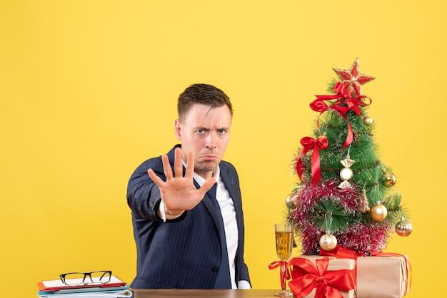 Вид спереди серьезного человека, показывающего знак остановки, сидящего за столом возле рождественской елки и подарков на желтом