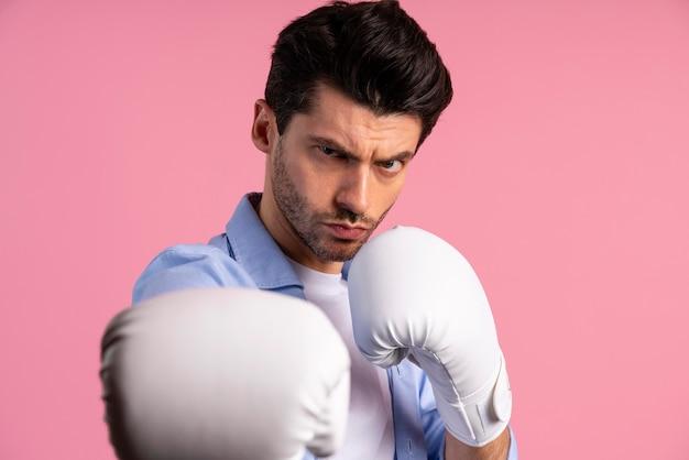 戦う準備ができているボクシンググローブを持つ真面目な男の正面図
