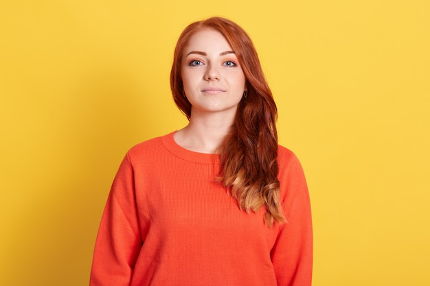 Вид спереди серьезной молодой привлекательной женщины с рыжими волосами в повседневном оранжевом свитере