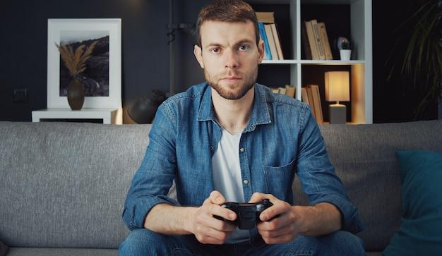 Вид спереди серьезного молодого человека, сидящего на диване и играющего в видеоигры с помощью джойстика с дистанционным управлением