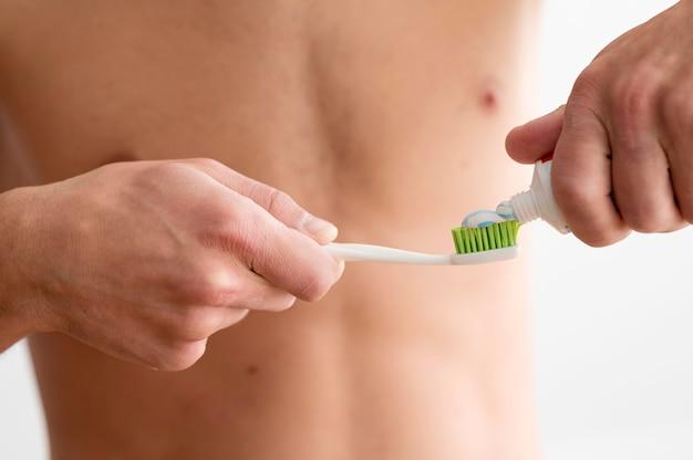 歯ブラシに歯磨き粉を塗る上半身裸の男の正面図