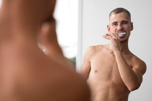 Вид спереди человека без рубашки, чистящего зубы в зеркале