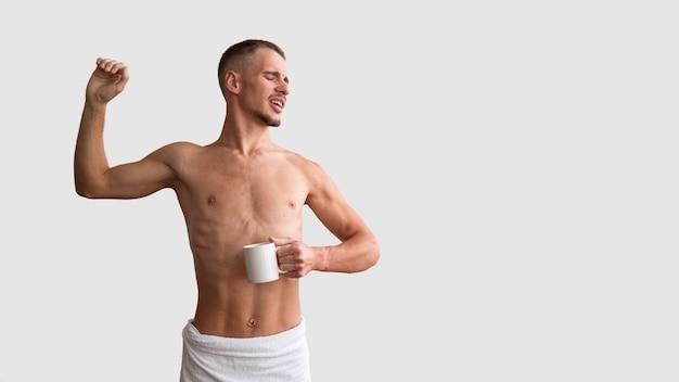 Вид спереди мужчины без рубашки, растягивающегося по утрам