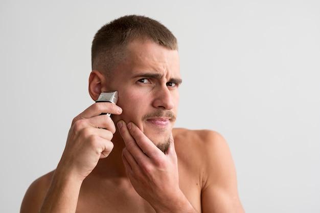 彼のひげに電気シェーバーを使用している上半身裸の男の正面図