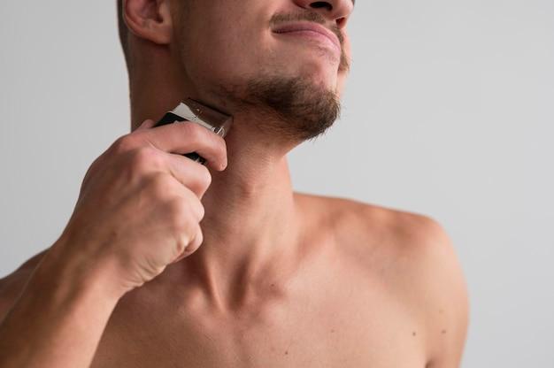 電気シェーバーを使用して上半身裸の男の正面図