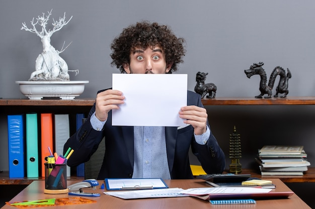 Вид спереди шокированного бизнесмена, держащего бумаги перед лицом в офисе