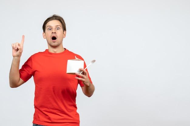 Вид спереди потрясенного эмоционального молодого парня в красной блузке, держащего бумажную коробку и указывающего вверх на белом фоне