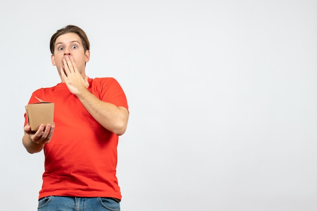 白い背景の上の小さなボックスを保持している赤いブラウスでショックを受けた感情的な若い男の正面図