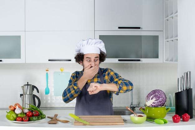 신선한 야채와 주방 도구로 요리하고 흰색 부엌에서 자신의 시간을 확인하는 충격을받은 남성 요리사의 전면보기