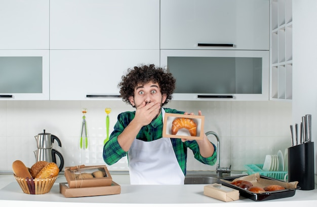 白いキッチンの小さな箱に焼きたてのペストリーを保持しているショックを受けた男の正面図