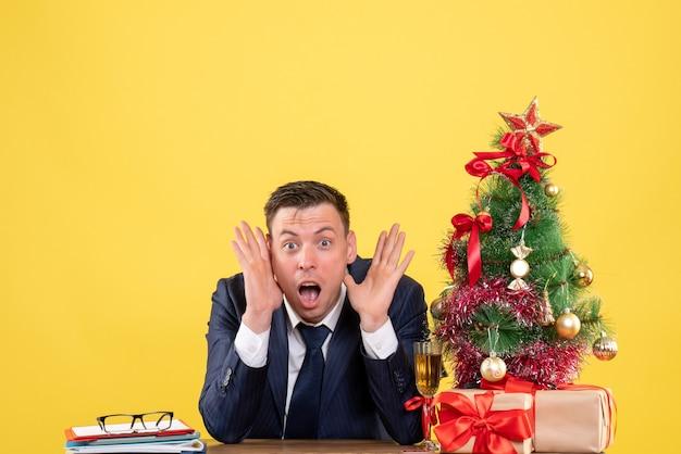 クリスマスツリーの近くのテーブルに座って、黄色で提示するショックを受けた男の正面図。