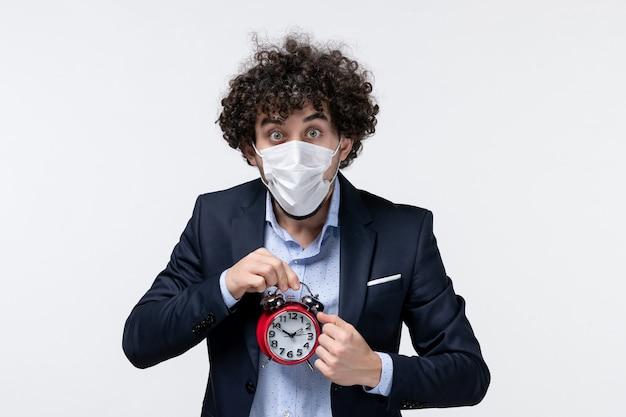 スーツを着て、時計を保持している彼のマスクを身に着けているショックを受けた驚いたビジネスパーソンの正面図