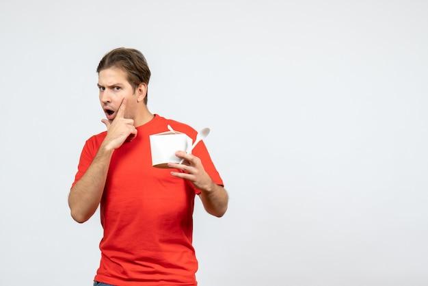 白い背景の上の紙箱とスプーンを保持している赤いブラウスでショックを受けた若い男の正面図