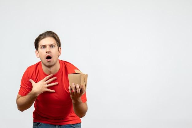 Вид спереди потрясенного молодого парня в красной блузке, держащего коробочку на белом фоне