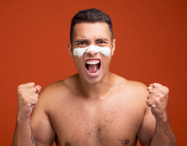フェイスマスクをつけた上半身裸の男の叫びの正面図