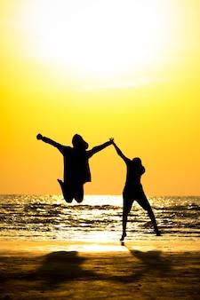실루엣 젊은 남자와 일몰 배경으로 바다 해변 위로 점프 하는 어린 소녀의 전면 보기.