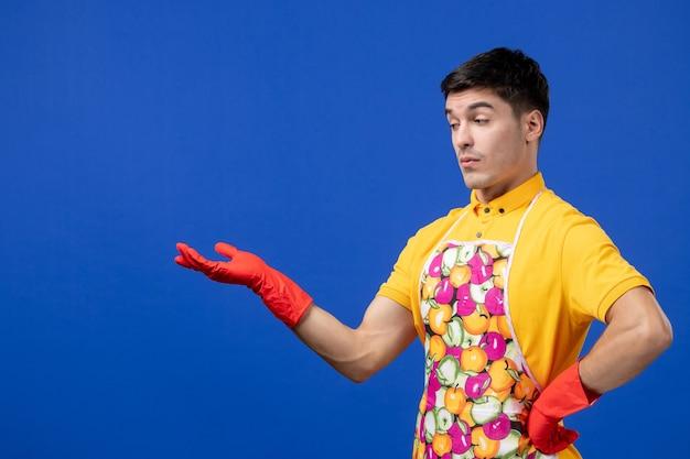 青い壁に立っているエプロンで懐疑的な男性の家政婦の正面図