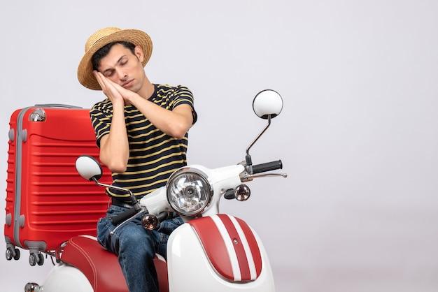 原付に麦わら帽子をかぶって眠っている若い男の正面図