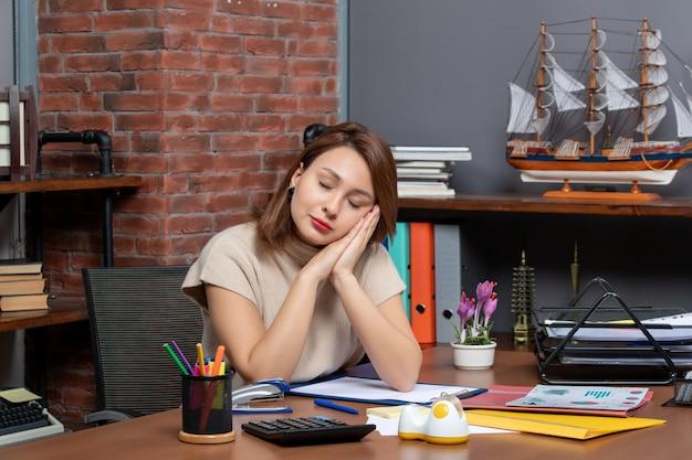 オフィスで働く手に参加することに頭を置く眠そうな女性の正面図