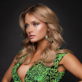 黒の孤立した背景に立ってポーズをとってスリムなブロンドの正面図。カメラを見て、スタジオで笑顔の緑のロングドレスの魅力的な若い女性。エレガンスとグラマーのコンセプト。