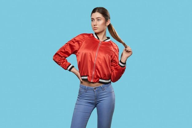 Вид спереди стройной молодой модели в спортивной куртке и джинсах