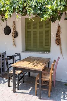 Вид спереди небольшой экстерьер кафе. стол и пустые стулья на открытом воздухе у белой стены. туристические места. типичный средиземноморский ресторан, место летнего отдыха. остров кос, греция