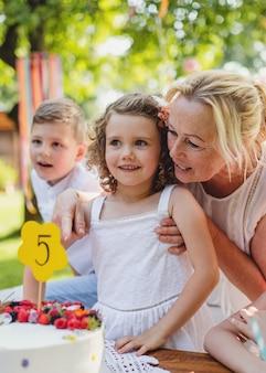 케이크와 할머니가 여름에 정원에서 야외에서 생일을 축하하는 어린 소녀의 전면 전망, 파티 컨셉입니다.