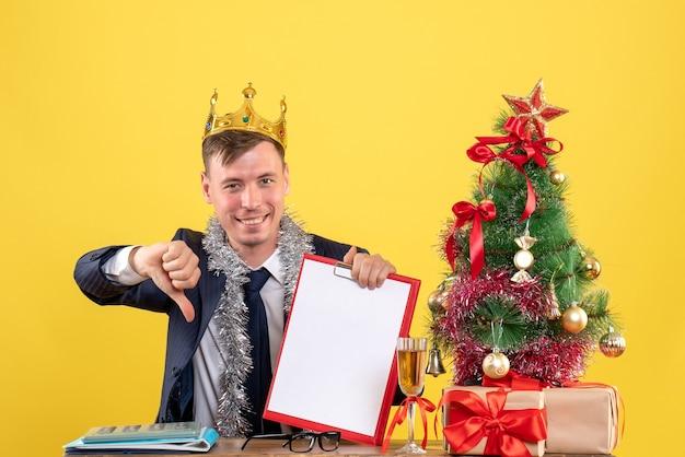 Вид спереди улыбающегося делового человека, делающего большой палец вниз знак, сидящего за столом возле рождественской елки и подарков на желтом