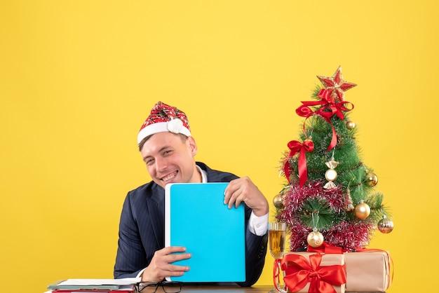 Вид спереди улыбающегося делового человека, сидящего за столом возле рождественской елки и подарков на желтом