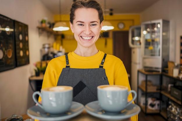 Вид спереди улыбающегося бариста, где подают чашки кофе