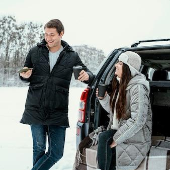 ロードトリップ中に車の横で温かい飲み物を楽しんでいる笑顔のカップルの正面図