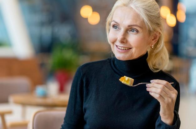 作業中にデザートを持つスマイリー長老ビジネス女性の正面図