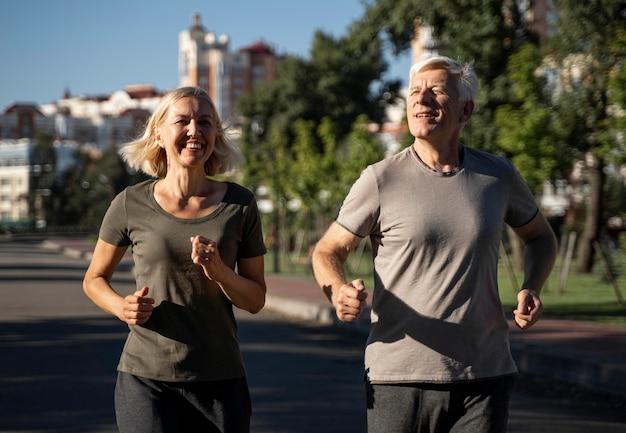 屋外でジョギングする笑顔の老夫婦の正面図