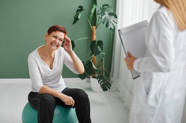 신체 운동을하는 covid 회복에 웃는 노인 여성의 전면보기