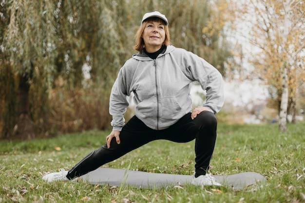 야외에서 운동 웃는 노인 여성의 전면보기