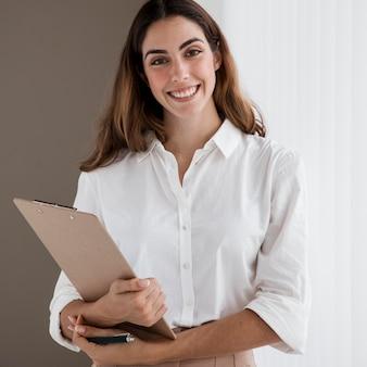 クリップボードを保持している笑顔のエレガントな実業家の正面図
