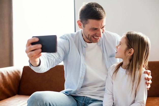 딸과 함께 selfie를 복용 웃는 아버지의 전면보기