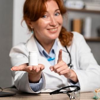 약 한 병을 제공하는 웃는 여성 의사의 전면보기
