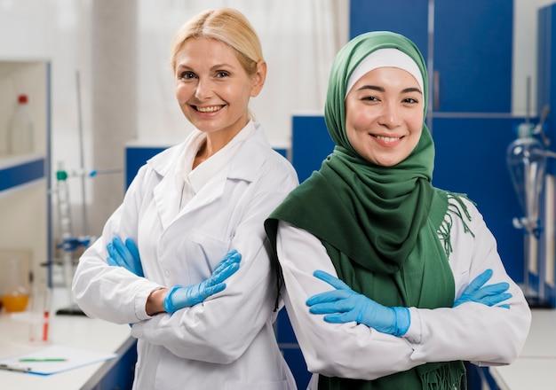 Вид спереди смайликов-ученых в лаборатории, позирующей со скрещенными руками
