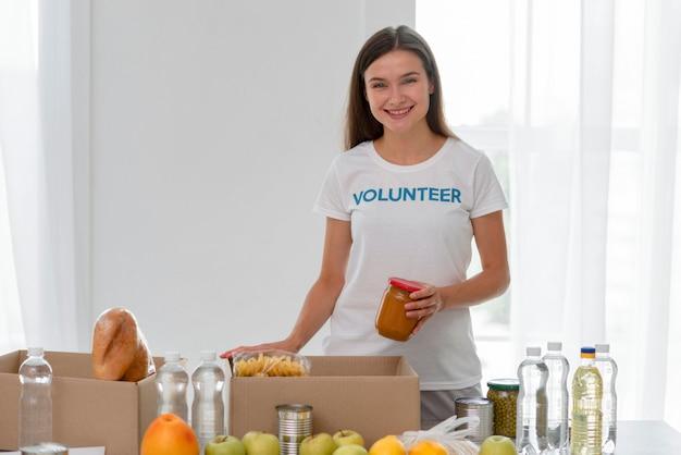 Вид спереди смайлика-волонтера-женщины, помогающего пожертвовать еду