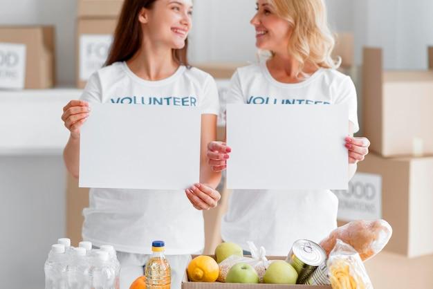 空白のプラカードと食品の寄付でポーズ笑顔の女性ボランティアの正面図