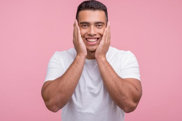彼の顔に手のひらでポーズをとって笑顔のハンサムな男の正面図