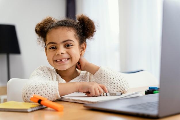ノートパソコンでオンライン学校の間に自宅で笑顔の小さな女の子の正面図