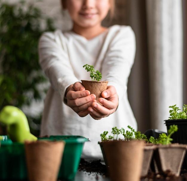 집에서 냄비에 식물을 들고 웃는 어린 소녀의 전면보기