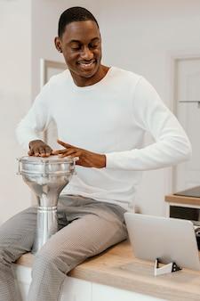 ドラムを演奏する自宅で笑顔の男性ミュージシャンの正面図