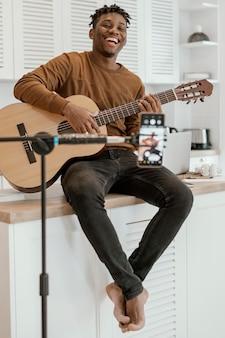 집에서 기타를 연주하고 휴대 전화로 녹음하는 웃는 남성 음악가의 전면보기